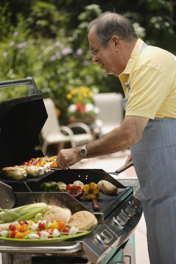 Senior Man Cooking on Barbecue
