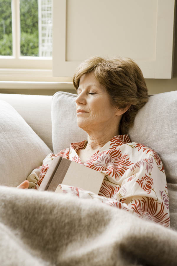Woman resting on couch with book