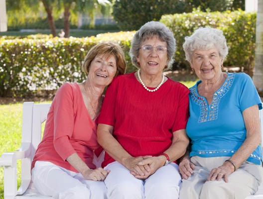 Portrait of three senior friends smiling in a park