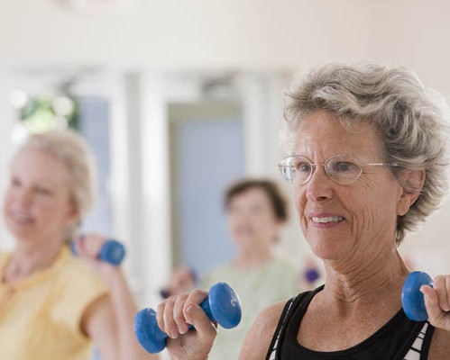 Senior women exercising with dumbbells in a health club