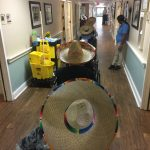 Residents making their way down the hall in sombreros greeting others.